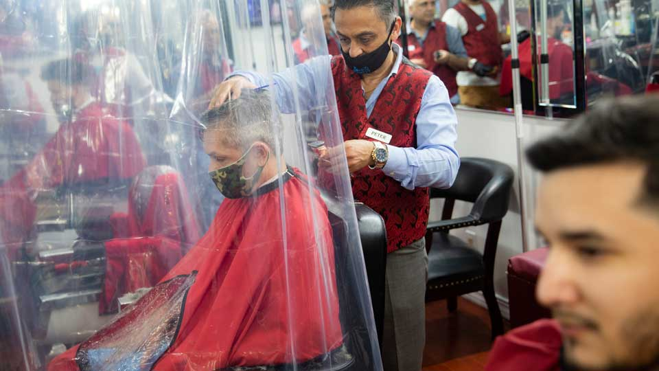Peter Shamuelov, center, wears a protective mask as he gives a haircut to a customer at Ace of Cuts barbershop, Monday, June 22, 2020, in New York