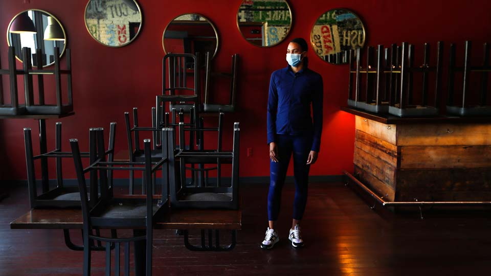 Stephanie Byrd, co-owner of The Block, poses for a photo with chairs on the tables while the restaurant is closed due to the coronavirus in Detroit