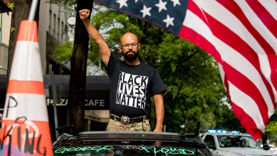 George Floyd's name is written on the windshield as John Coy wears a shirt that reads Black Lives Matter and stands through his sunroof with his fist in the air at 16th Street Northwest renamed Black Lives Matter Plaza near the White House