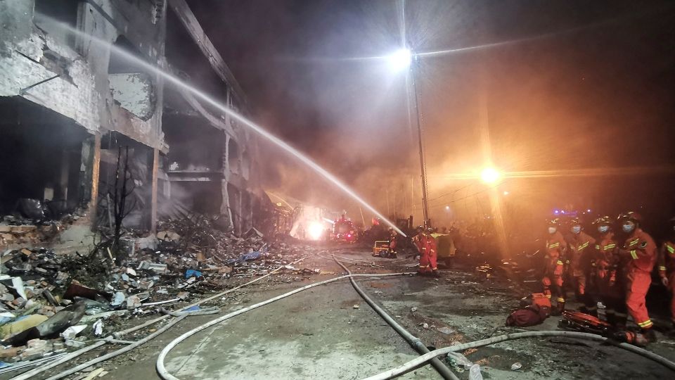 In this photo released by Xinhua News Agency, firefighters work at the site of buildings damaged after a tanker truck explosion on a highway in Wenling.