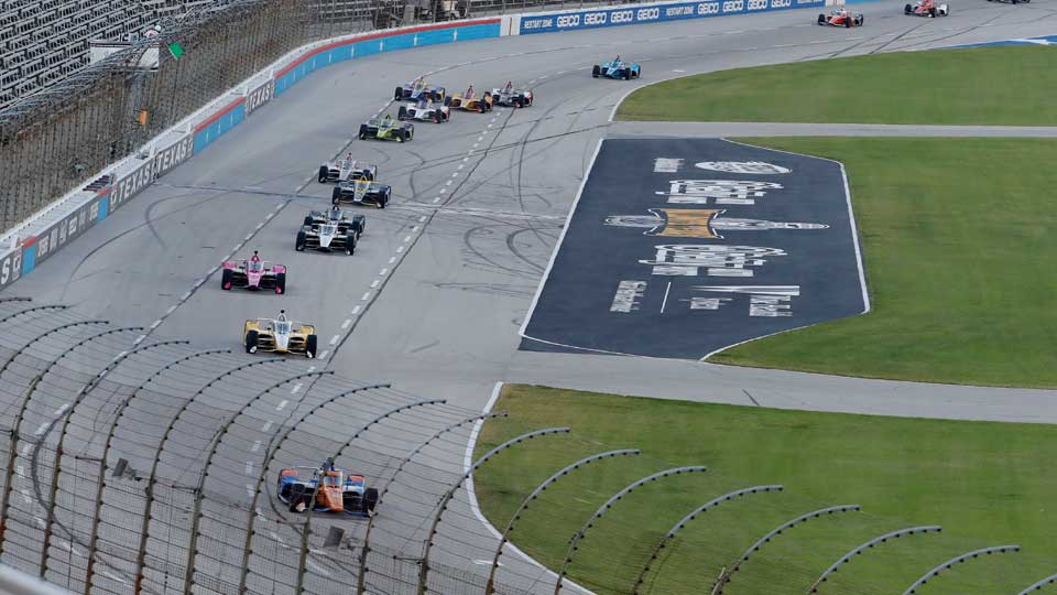 Scott Dixon, bottom, leads the field into Turn 1 during an IndyCar auto race at Texas Motor Speedway
