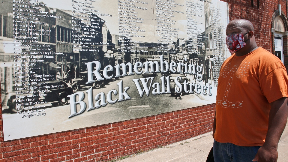 Freeman Culver stands in front of a mural listing the names of businesses destroyed during the Tulsa race massacre in Tulsa, Okla.