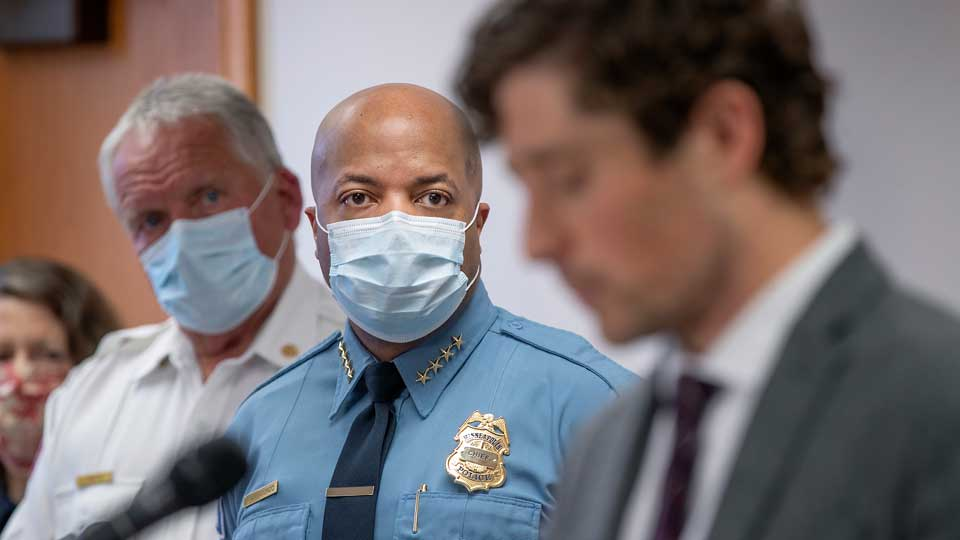 Minneapolis Police Chief Medaria Arradondo, center, listens as Minneapolis Mayor Jacob Frey becomes emotional during a news conference