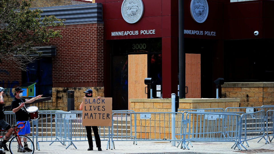 Doors are boarded up as protesters gather at the Minneapolis Police Third Precinct Wednesday, May 27, 2020.