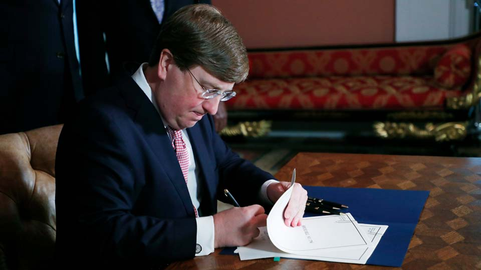 Mississippi Gov. Tate Reeves signs the bill retiring the last state flag in the United States