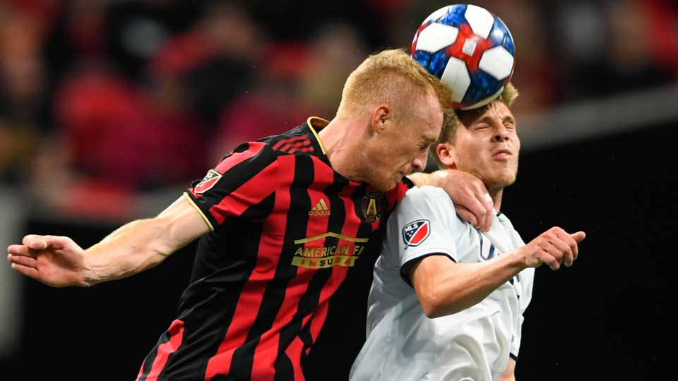 Atlanta United defender Jeff Larentowicz, left, and New England Revolution midfielder Scott Caldwell