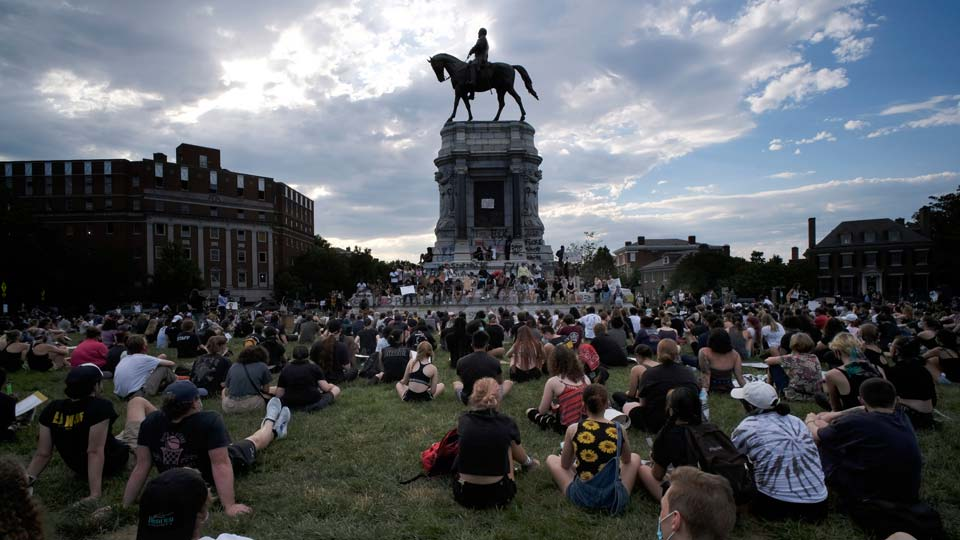 Protesters sit near the statue of Robert E. Lee on Monument Avenue in Richmond, Va.