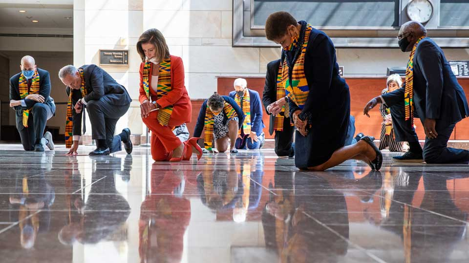 House Speaker Nancy Pelosi of Calif., center, and other members of Congress, kneel and observe a moment of silence at the Capitol's Emancipation Hall