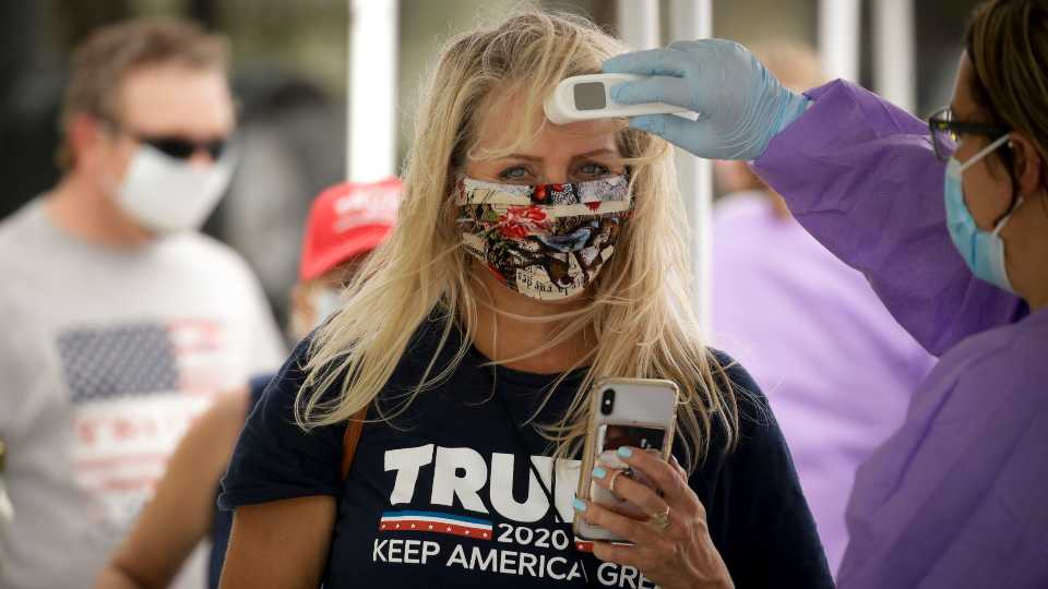 A supporter gets her temperature checked prior to attending a campaign rally for President Trump at the BOK Center in Tulsa, Okla., Saturday, June 20, 2020.
