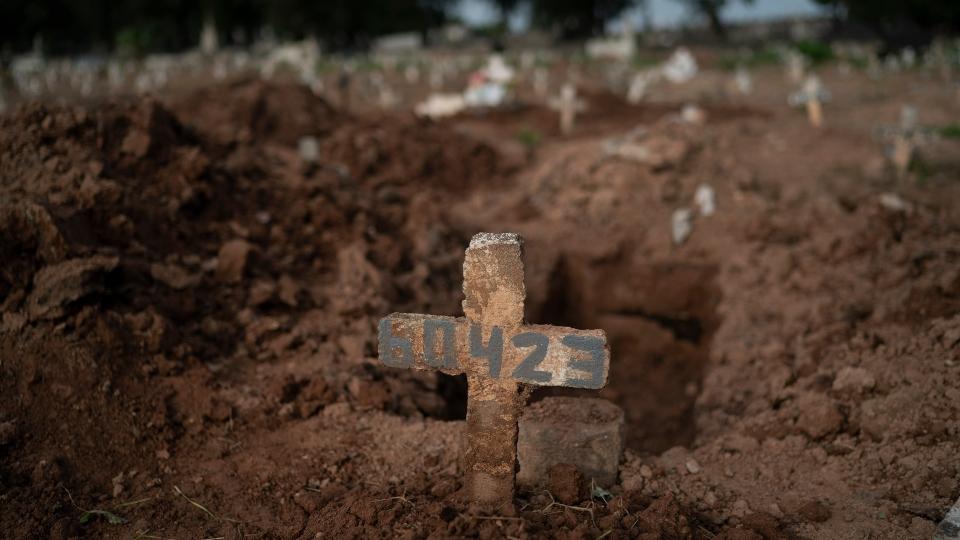 A cross marks the grave of 57-year-old Paulo Jose da Silva, who died from the new coronavirus, in Rio de Janeiro, Brazil