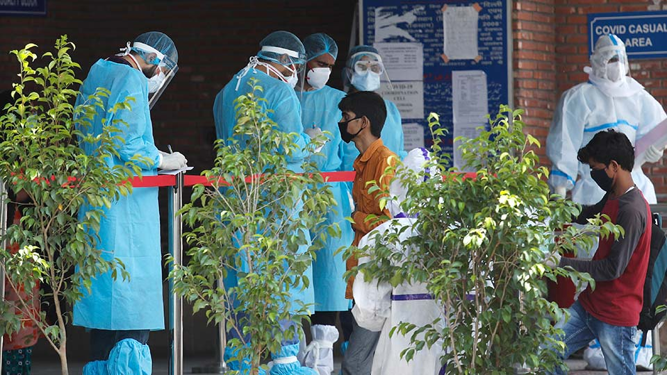Doctors in personal protective suits check the papers of people whose relatives are admitted in a COVID-19 government designated hospital, in New Delhi, India Tuesday, June 23, 2020.