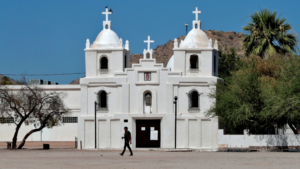 In this June 13, 2020, photo, a man walks past Our Lady of Guadalupe church in Guadalupe, Ariz.