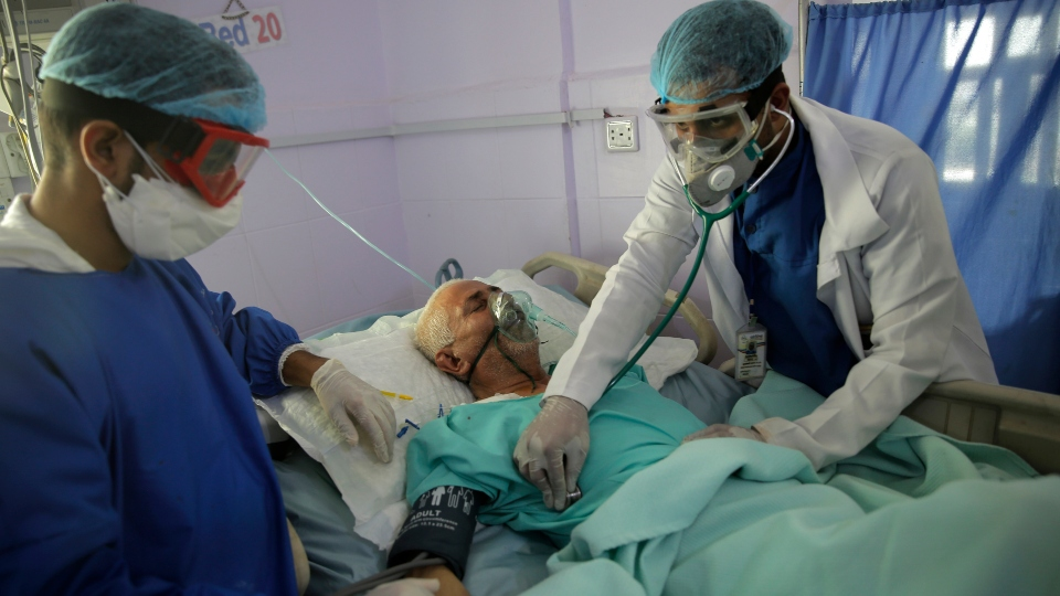 In this Sunday, June 14, 2020 file photo, medical workers attend to a COVID-19 patient in an intensive care unit at a hospital in Sanaa, Yemen.