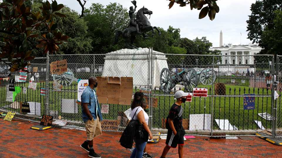 People wear face masks to protect against the spread of the new coronavirus as they walk past protest signs affixed to fencing surrounding a statue of President Andrew Jackson in Lafayette Park near the White House in Washington, Saturday, June 20, 2020.