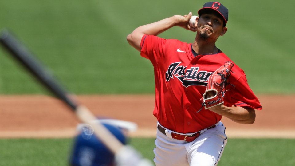 Cleveland Indians starting pitcher Carlos Carrasco, top, delivers to Kansas City Royals' Whit Merrifield in the first inning in a baseball game Sunday, July 26, 2020, in Cleveland.