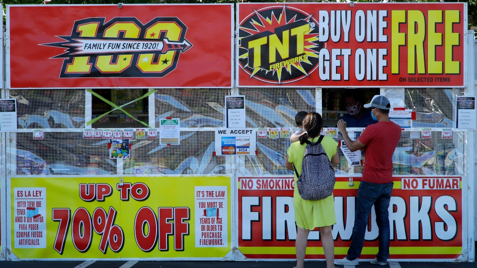 People purchase fireworks on Thursday, July 2, 2020, in Dublin, Calif. For many Americans, the Fourth of July won't be about big festivities but setting off fireworks themselves.