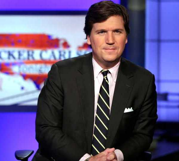"In this March 2, 2017 file photo, Tucker Carlson, host of ""Tucker Carlson Tonight,"" poses for photos in a Fox News Channel studio, in New York. Tucker Carlson's top writer has resigned from Fox News after secretly posting racists and sexist remarks online. CNN reported Friday, July 10, 2020 that writer Blake Neff used a pseudonym to write bigoted comments about Black and Asian people, as well as women, on the online platform AutoAdmit."