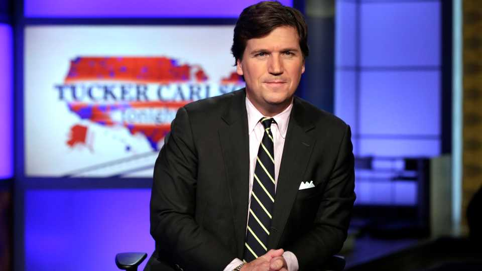"""In this March 2, 2017 file photo, Tucker Carlson, host of """"Tucker Carlson Tonight,"""" poses for photos in a Fox News Channel studio, in New York. Tucker Carlson's top writer has resigned from Fox News after secretly posting racists and sexist remarks online. CNN reported Friday, July 10, 2020 that writer Blake Neff used a pseudonym to write bigoted comments about Black and Asian people, as well as women, on the online platform AutoAdmit."""