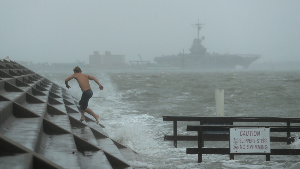 A man jumps from a wave as Hurricane Hanna begins to make landfall, Saturday, July 25, 2020, in Corpus Christi, Texas.