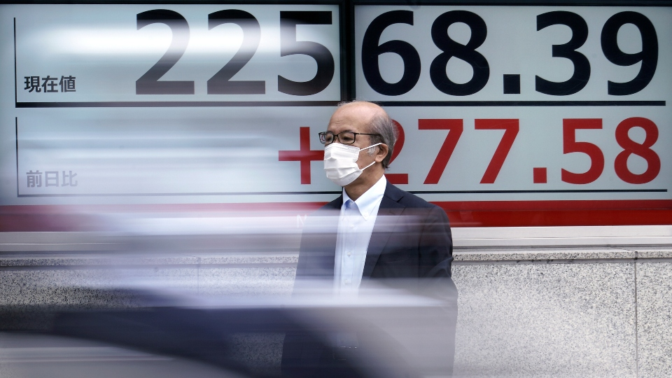 A man wearing a face mask to help curb the spread of the coronavirus stands near an electronic stock board showing Japan's Nikkei 225 index at a securities firm in Tokyo Monday, July 13, 2020.