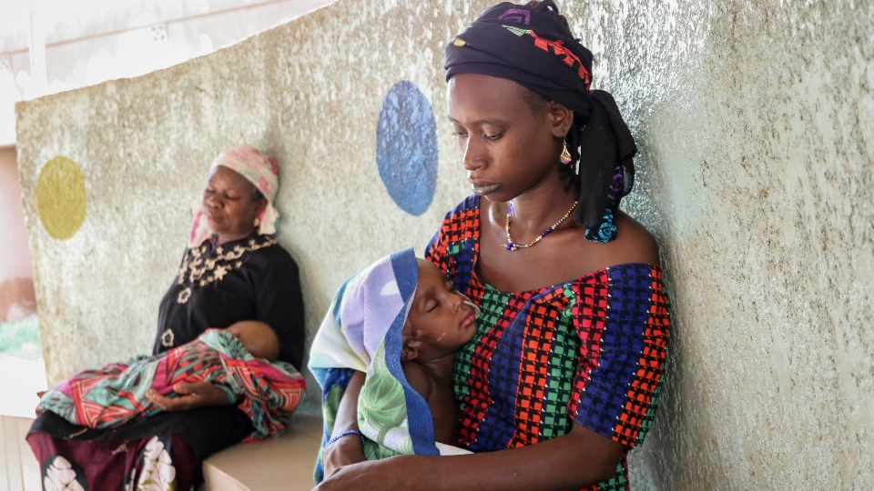 Fatima Li, 20, foreground, holds her two-year-old son, Hama Sow, as he is treated with a feeding tube for malnourishment