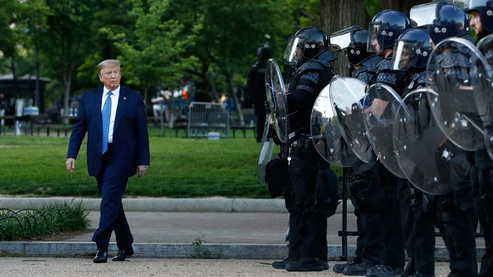 President Donald Trump walks past police in Lafayette Park