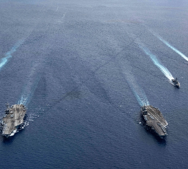 n this photo provided by U.S. Navy, the USS Ronald Reagan (CVN 76) and USS Nimitz (CVN 68) Carrier Strike Groups steam in formation, in the South China Sea, Monday, July 6, 2020.