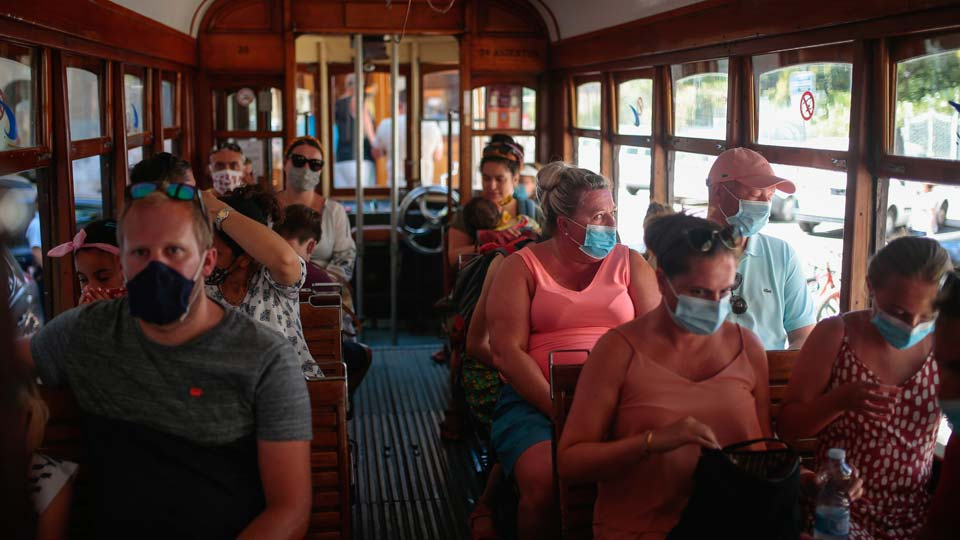Tourists and locals ride a tram in town of Sóller in the Balearic Island of Mallorca, Spain