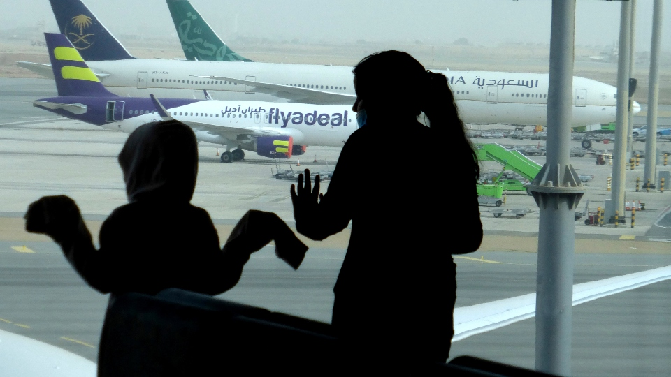 Passengers watch aircraft on the tarmac as they wait for their flight at the King Abdulaziz International Airport in Jiddah, Saudi Arabia, Tuesday, July 28, 2020.