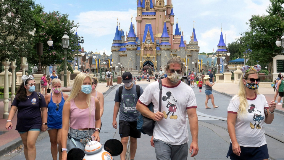 In this Saturday, July 11, 2020, file photo, guests wear masks as required to attend the official reopening day of the Magic Kingdom at Walt Disney World in Lake Buena Vista, Fla.