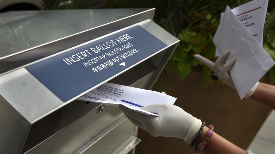 In this July 7, 2020, file photo a woman wearing gloves drops off a mail-in ballot at a drop box in Hackensack, N.J.