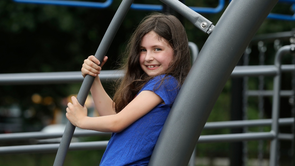 Sophia Garabedian, 6, of Sudbury, Mass., who contracted Eastern Equine Encephalitis in 2019, stands for a photograph on a playground, Wednesday, July 8, 2020, in Sudbury.