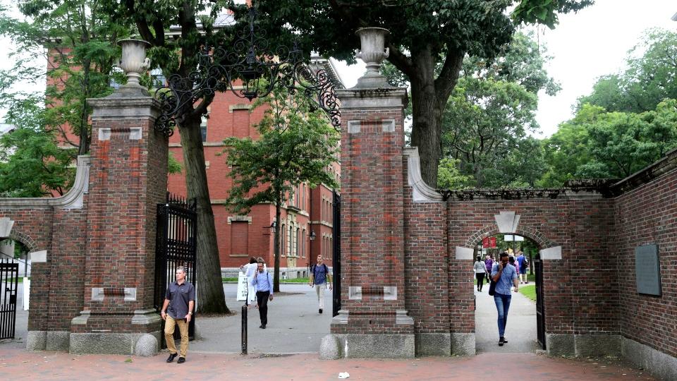 In this Aug. 13, 2019, file photo, pedestrians walk through the gates of Harvard Yard at Harvard University in Cambridge, Mass.