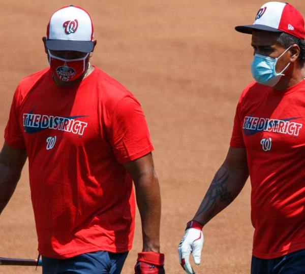 Washington Nationals' manager Dave Martinez, left, and bullpen coach Henry Blanco walk together during a baseball training camp workout at Nationals Stadium, Sunday, July 5, 2020