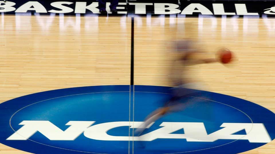 player runs across the NCAA logo