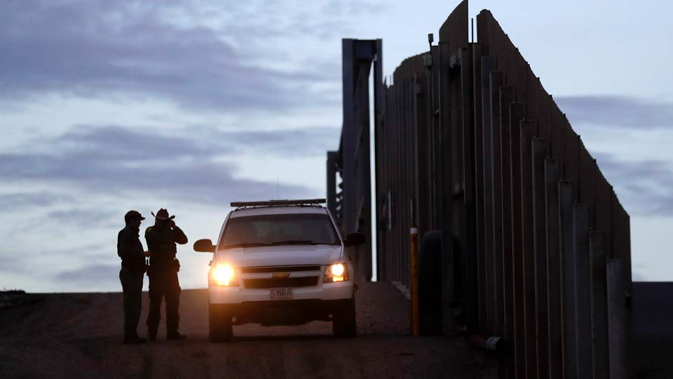 United States Border Patrol agents stand by a vehicle near one of the border walls separating Tijuana, Mexico and San Diego