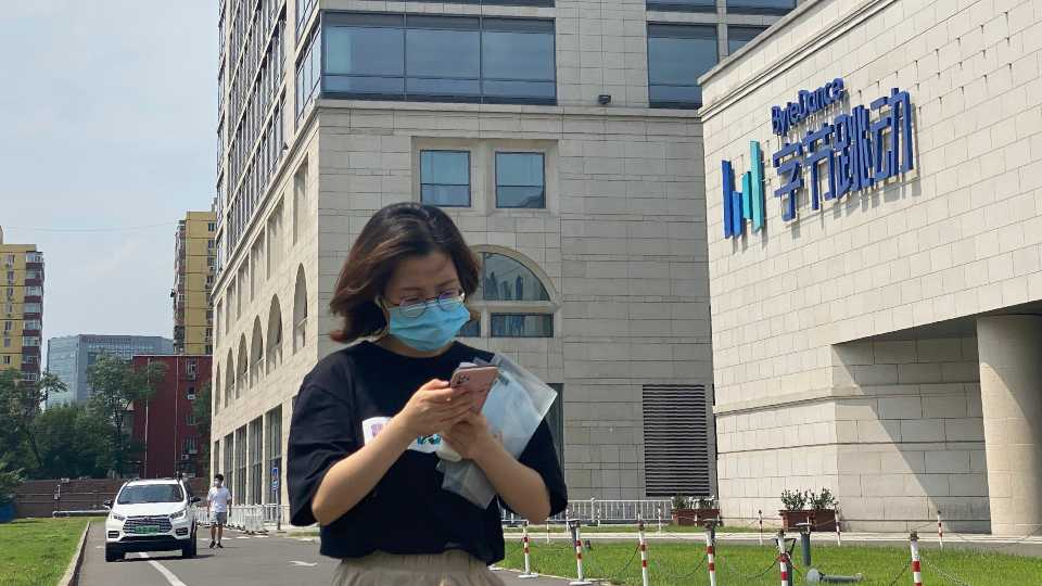 A woman uses her phone as she passes by the ByteDance headquarters in Beijing, China, on Friday, Aug. 7, 2020. The Chinese government is complicating the U.S.-government-ordered sale of U.S. TikTok assets. China on Friday, Aug. 28, 2020 introduced export restrictions on artificial intelligence technology, seemingly including the type that TikTok uses to choose which videos to spool up to its users. That means TikTok's Chinese owner, ByteDance, would have to obtain a license to export any restricted technologies to a foreign company.