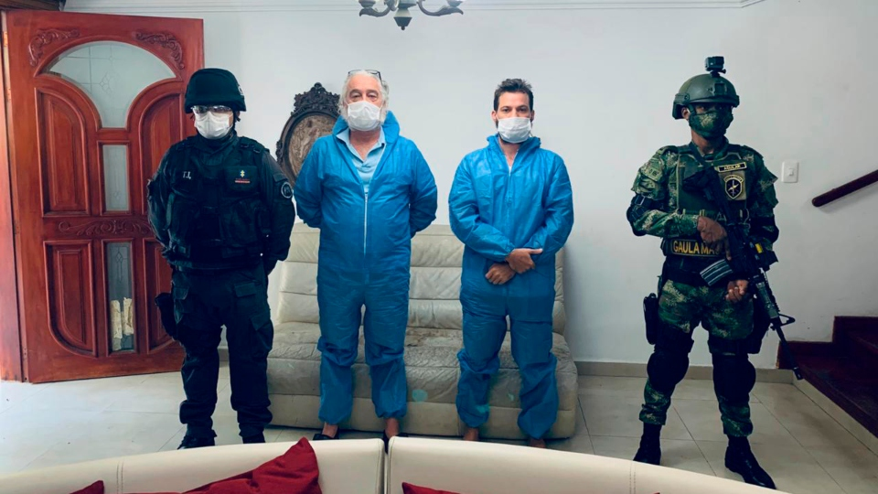 In this photo released by Colombia's Prosecutor's Press Office, a police officer and a soldier flank Mark Grennon, second left, and his son Joseph Grennon, during a raid in Santa Marta, Colombia.