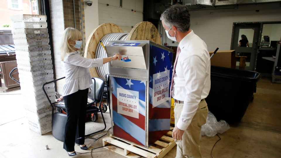 In this May 27, 2020, file photo, Bucks County commissioners Diane Ellis-Marseglia, left, and Robert Harvie unpack a new ballot drop box at the county's administration building prior to the primary election in Doylestown, Pa.