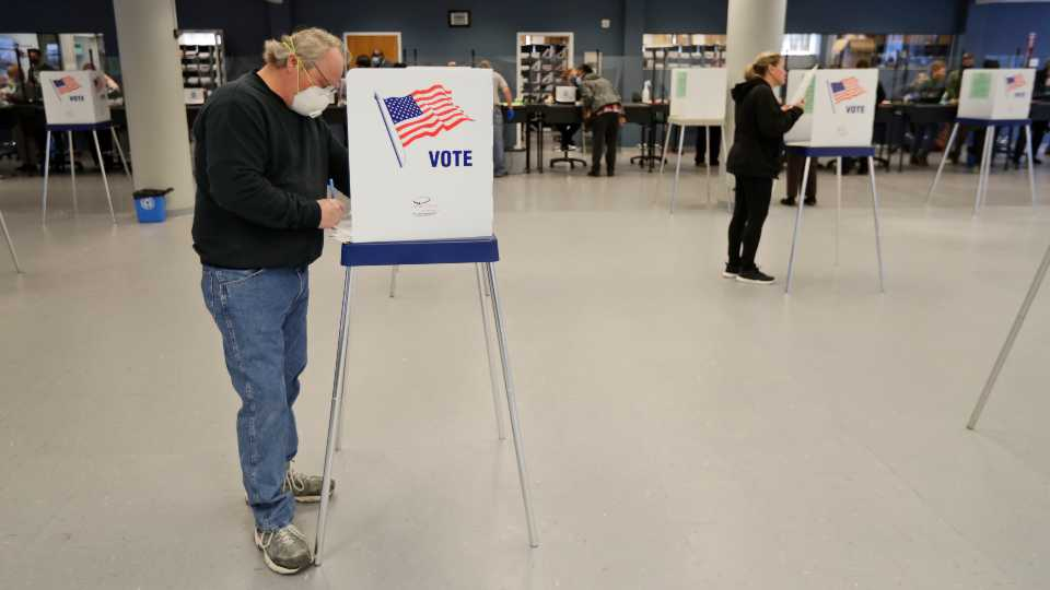This Tuesday, April 28, 2020 file photo shows Jerome Fedor, left, voting using social distancing at the Cuyahoga County Board of Elections, in Cleveland, Ohio. Ohio's elections chief says his office plans to remove about 120,000 inactive Ohio voter registrations from state voter rolls after the November election.