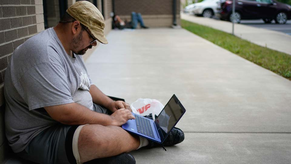 Barlow Mitchell sits outside the Lee County Public Library while using the public WIFI, in Beattyville, Ky.