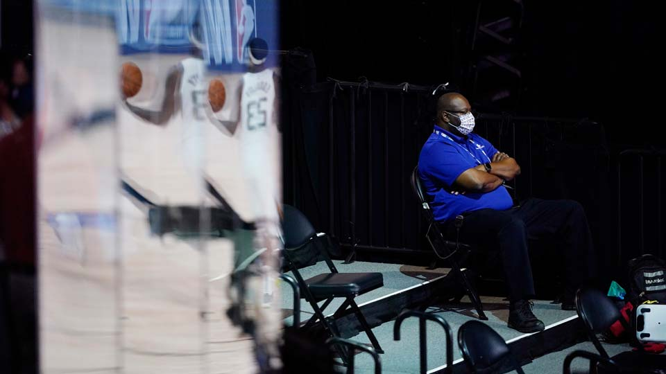 A man wearing a mask watches during halftime of an NBA basketball game between the Utah Jazz and the Oklahoma City Thunder, Saturday, Aug. 1, 2020, in Lake Buena Vista, Fla.