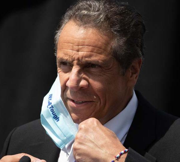 New York Gov. Andrew Cuomo removes a mask as he holds a news conference in Tarrytown, N.Y.