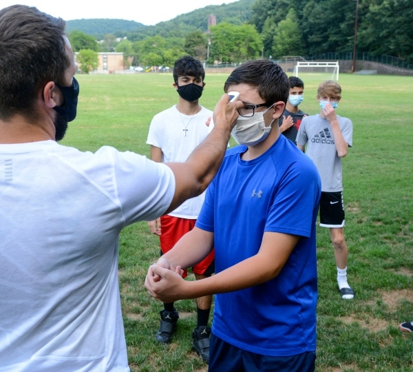 Head coach Zachary Reichert, left, takes Nicholas Giuffre's temperature prior to the start of Pottsville's boys' soccer practice at Alumni Field in Pottsville, Pa., Thursday, Aug. 6, 2020.