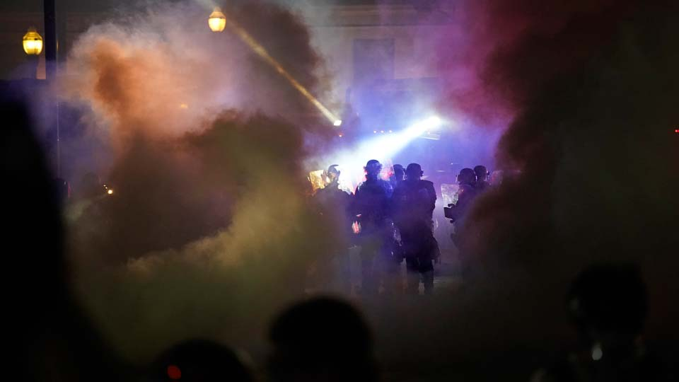 Police in riot gear clear the area