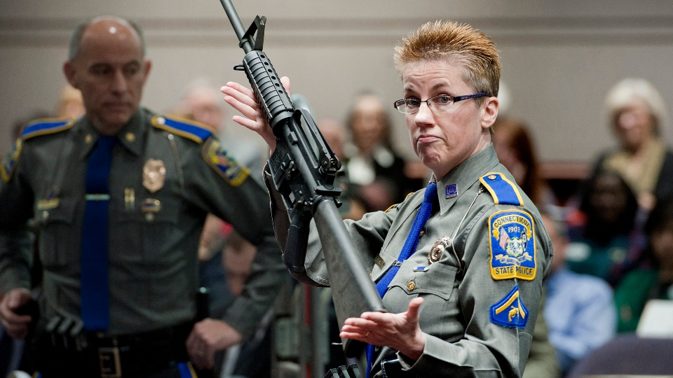 In this Jan. 28, 2013, file photo, firearms training unit Detective Barbara J. Mattson, of the Connecticut State Police, holds up a Bushmaster AR-15 rifle made by Remington Arms, the same make and model of the gun used by Adam Lanza in the December 2012 Sandy Hook School shooting.