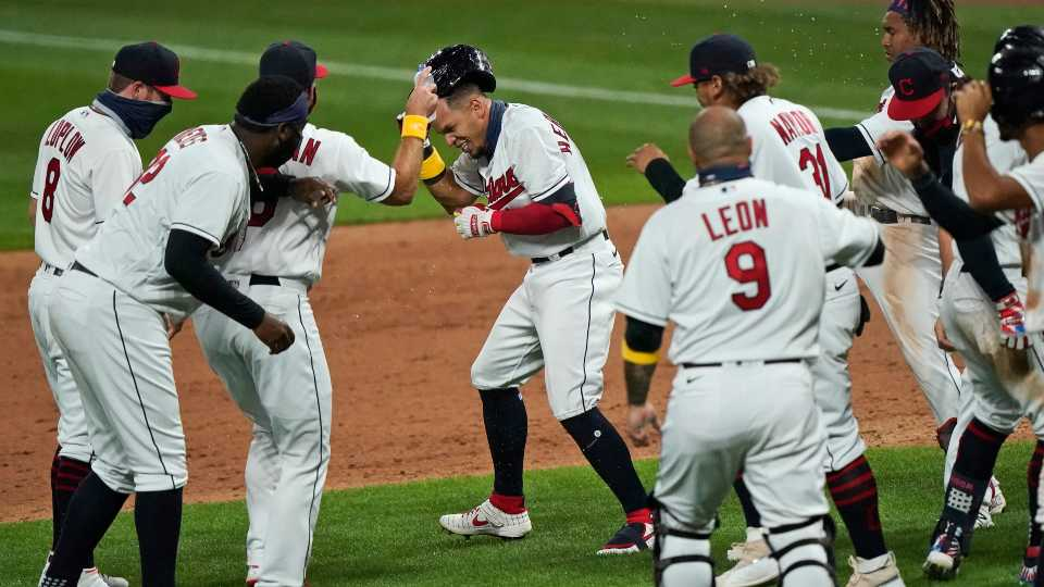 Cleveland Indians' Cesar Hernandez, center, is mobbed by teammates after hitting an RBI-single in the ninth inning in a baseball game against the Milwaukee Brewers, Saturday, Sept. 5, 2020, in Cleveland.