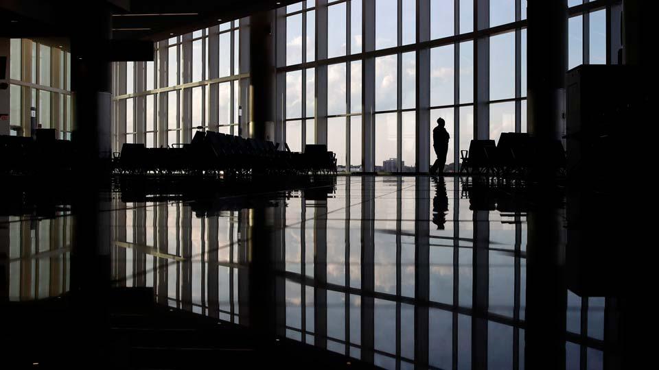 A woman looks through a window at a near-empty terminal at an airport in Atlanta