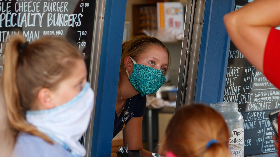 In this Aug. 4, 2020 file photo, a staffer wears a mask while taking orders at a small restaurant in Grand Lake, Colo., amid the coronavirus pandemic.