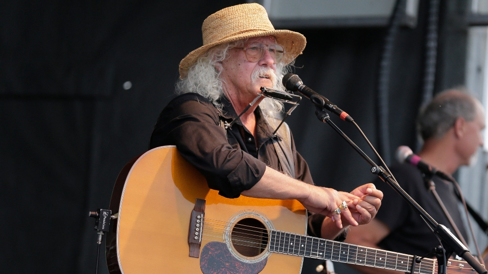 In this Aug. 15, 2020 file photo Arlo Guthrie talks during a concert at a Woodstock 50th anniversary event in Bethel, N.Y.